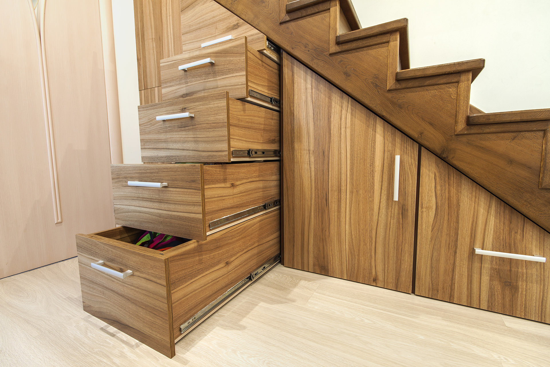 Modern architecture interior with  luxury hallway with glossy wooden stairs in modern storey house. Custom built pullout cabinets on glides in slots under stairs